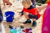 A young child makes colourful art on the beach