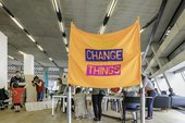 A large orange banner with the words 'change things' written on it