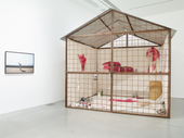 Nikhil Chopra installation in the gallery at Kettle's Yard, a cross section of a single room structure, enclosed by a wire wall, with red murals within