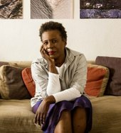 Author Claudia Rankine sitting on a sofa looking into the camera