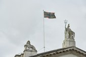 A black, green and red version of the union jack flag flying above Tate Britain
