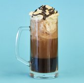 a tall glass with a handle is filled with coke and topped with ice cream and chocolate sauce. presented on a blue background.
