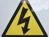 triangular electrical danger sign in yellow with a lightening bolt with an arrow at the end