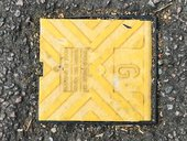 Square yellow electrical or gas plastic flap on the road surrounded by tarmac