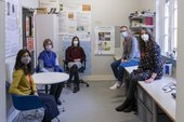 Five people pose in an office, some sitting on chairs, some perched on the edge of a desk, all looking towards the camera. They are distanced and wearing face masks to help prevent the spread of Covid-19.