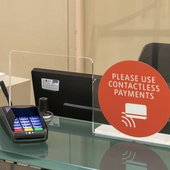 Card machine and a sign saying please use contactless payments.