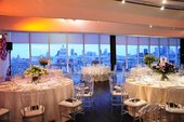 A series of tables covered in white cloth with flowers and the London skyline in the background