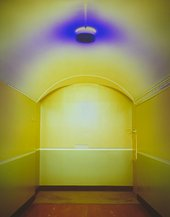 Photograph of a yellow painted corridor with a blue ceiling light