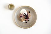 photograph of a slice of courgette cake on a place with blueberries and cream freche