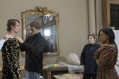 people tailor a costume in front of a mirror