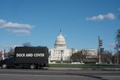 A truck parked in front of the US Capitol building with the words 'Duck and Cover' on an LED screen