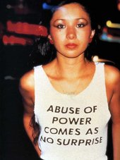 Woman wearing a white vest with the slogan 'Abuse of power comes as no surprise'