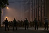 film still of police standing in a city protecting against a riot