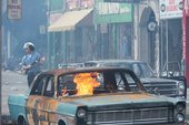 an armed policeman walks behind a car on fire