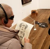 Image of a visually impaired visitor checking an artwork