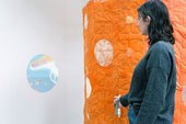 a person stands by an orange quilted wall and a circular projection