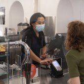 a person stands at a till desk and orders something from a member of cafe staff