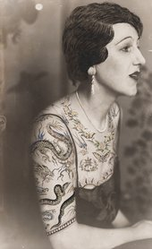 Black and white photograph of a woman sitting in profile, the bust dressed in a blouse made of tattoo patterns drawn on the photograph