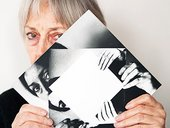 Dóra Maurer covers half her face with a mise-en-abime photograph of herself doing the same pose