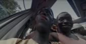 A group of people sitting in a car shot from a low angle