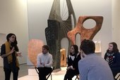 A group of four people sit in an art gallery in front of a display of sculptures, listening to someone speak. The speaker is standing and gesticulating with their hands.