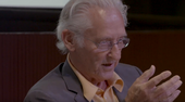 film still of ed ruscha sitting down in a suit and talking in front of a live audience