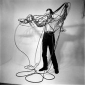 man stood with arms outstretched holding a mass of knotted wires.