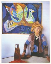 Eileen Agar wearing her Glove Hat 1936 and standing by her painting The Bird's Nest 1969 at her home in London, 1989
