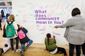 A group of people look at text that says 'what does community mean to you?'