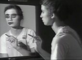 Still from Video Art black and white image of girl in front of a mirror with paint over her eye.