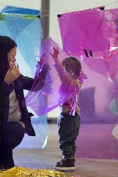 A child and parent play in a making workshop, surrounded by translucent cellophane