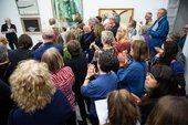 Poet Ella Frears reads to an applauding audience in front of artworks at Tate St Ives