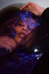 Photo of woman lying in bath with netting over her face