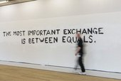 A man walks past a display with the words 'The most important exchange is between equals'