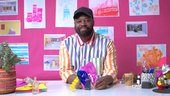 a man sits against a pink backdrop with artworks on paper behind him on the wall, holding a sensory sculpture