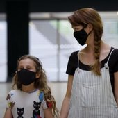 a parent and child wearing face coverings walking into the gallery.