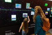 Family interacting with a large digital touch screen displaying artwork images