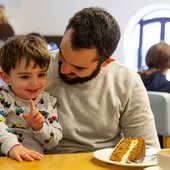 a parent and child sat at a table with a slice of cake and a coffee.