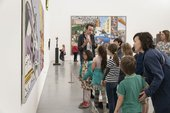 a group of children stand in front of Lichtenstein's Whaam! in the sixty years display in Tate Britain