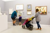 two people with a pram and a young child stands in the Tate St Ives gallery