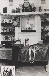 An interior scene showing a bed, framed photographs, a garment and a bag, with various ornaments and a clock in the background.