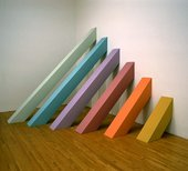 Fig.12 Sculpture by Judy Chicago installed in a gallery featuring 6 square planks running from floor to wall; each is painted a different colour and the length varies by increments, with the shortest nearest the camera