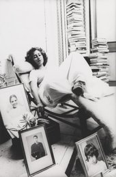 A figure lies on a reclining chair in an indoor setting, surrounded by framed portrait photographs and stacks of books.