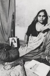 A figure sits on the floor in an indoor setting, surrounded by a cloth bag, an axe, a staff, a notebook and pen, some jewellery, a photograph and some loose grain.
