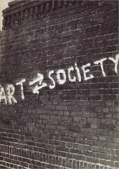 Black-and-white photograph of a brick wall with white graffiti on it reading ART SOCIETY with two arrows between the two words, the upper pointing right (towards SOCIETY), the lower pointing left (towards ART)