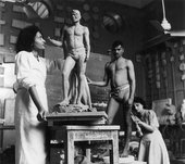 An artist's studio setting in which a figure stands looking up at a sculpture of a male body, while another figure crouches down next to a live model.