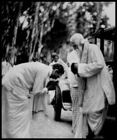 Black-and-white photography of two people, one bowing deeply to the other