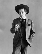 Fig.3 Black-and-white studio portrait photograph of Ed Ruscha dressed as a cowboy, left hand in his pocket, right hand holding a cigarette like a gun pointed to the camera