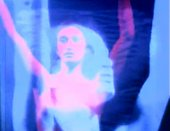Still image from a video by Nam June Paik featuring layered images of a woman's face with arms in the air in shades of purple, blue and pink