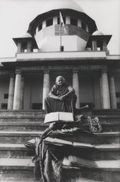 A figure sits at the top of some steps leading up to a large building with columns, with documents, a framed portrait and swathes of cloth placed on the steps in front of them.